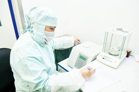balanza de laboratorio: Farmacéutica hombres investigador científico en uniforme protector trabajar con escalas digitales en laboratorio de fábrica Fabricación de la industria farmacéutica. datos de la escritura del trabajador después de la ponderación