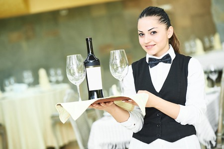 Attractive young female waitress holding a tray with bottle of wine and glasses at restaurant or cafe Standard-Bild