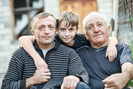grandad: Multi generation portrait of happy grandfather with his son and grandson sitting in front of the country house