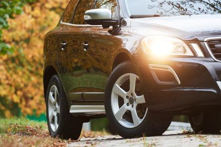 Stad verkeersveiligheid. SUV automobielwagen met koplamp ingeschakeld in de herfst. Stockfoto