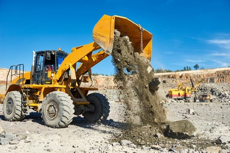 extracting: Heavy wheel loader extracting granite rock or iron ore at opencast mining quarry