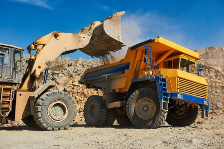 Heavy wheel loader excavator loading granite rock or iron ore into the huge dump truck at opencast mining quarry
