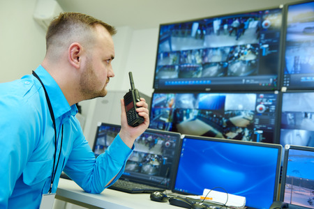 monitoring system: security guard officer watching video monitoring surveillance security system Stock Photo