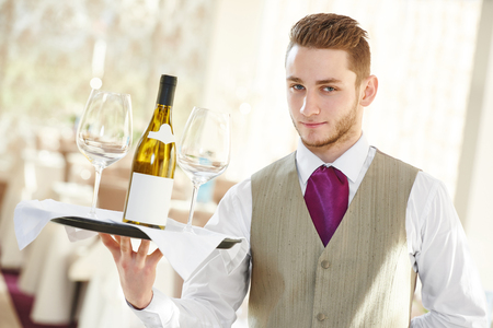 Handsome male waiter holding a tray with bottle of wine and glasses at restaurant or cafe