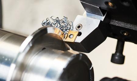 金属加工業。CNC 精密切削鋼メタル ディテール加工ワーク ショップで旋盤に。ツールの選択と集中