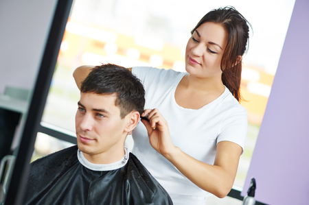 Female hairdresser cutting hair of smiling man client at beauty parlour salon