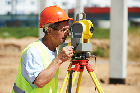 teodolito: Portrait of builder worker with theodolite transit equipment at construction site outdoors during surveyor work