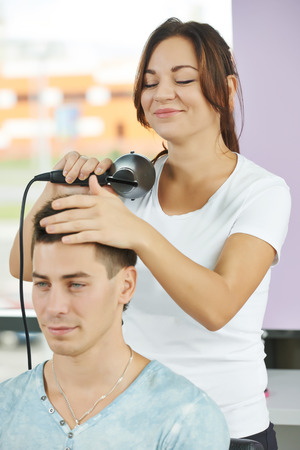 blow dryer: Female hairdresser drying hair with blow dryer of man client at beauty parlour Stock Photo