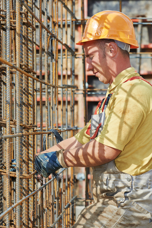 concrete form: builder worker knitting metal rods bars into framework reinforcement for concrete pouring at construction site Stock Photo