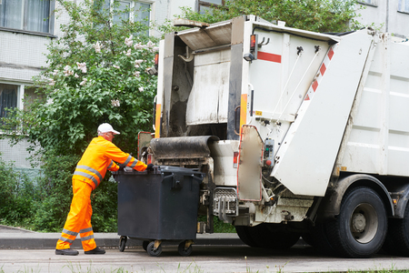 Worker of urban municipal recycling garbage collector truck loading waste and trash bin Foto de archivo