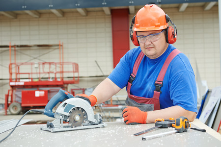 power tool: Male builder working with power tool circular saw machine cutting plastic parts at construction site