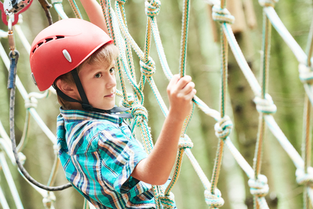 Adventure rope way and extreme activity. Scout boy climbing on high wire park in the forest