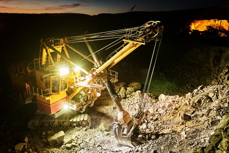 Mining industry. Heavy excavator digging granite rock or iron ore at dusk construction opencast quarry. Stock Photo