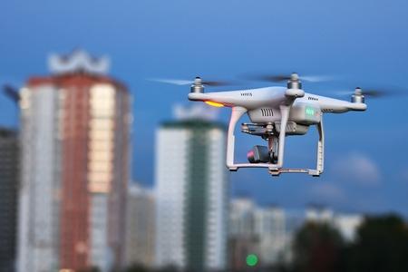 Drone quadcopter met een hoge resolutie digitale camera vliegen of zweven in de blauwe lucht boven de stad Stockfoto - 65820821