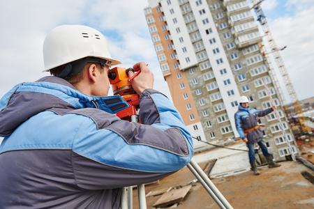 teodolito: Dos trabajadores de constructores con equipos de tránsito teodolito en el sitio de construcción al aire libre durante el trabajo de topógrafo