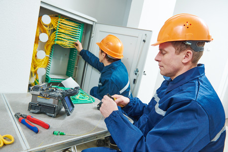 połączenie internetowe. technik inżynier pracujący przy maszynie złączenia fuzyjnego łuk podczas podłączania kabla światłowodowego. Zdjęcie Seryjne