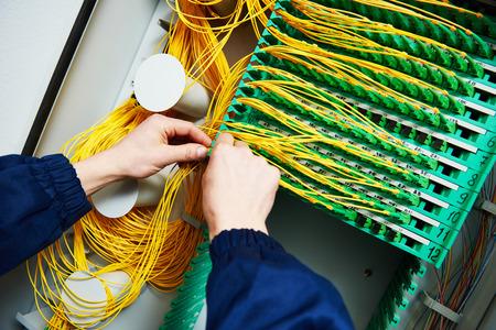 インターネット接続。テクニシャン エンジニア手接続する光ファイバーケーブル