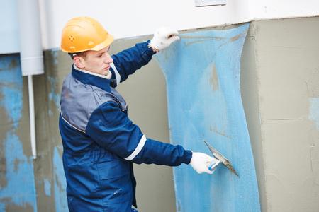 fiberglass: De fibra de vidrio de refuerzo enlucido de malla utilizada para la escayola. trabajador de la construcción en la pared de la fachada enyesado con el flotador espátula