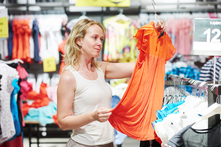 woman choosing dress during shopping at garments apparel clothing shop Stock Photo