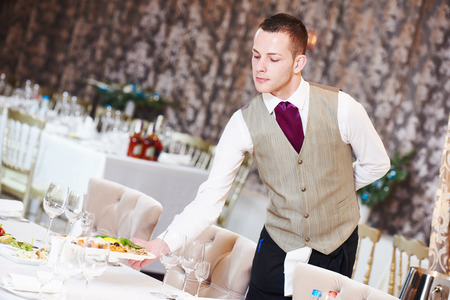 hotel staff: Restaurant service or waiter occupation. Handsome male worker serving table with food plates at catering in cafe Stock Photo