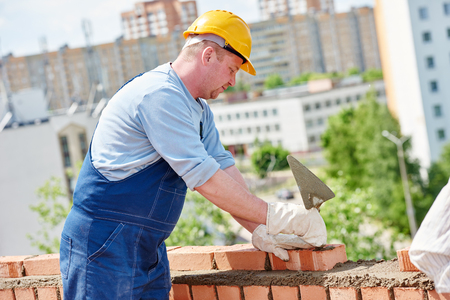 brick mason: Bricklaying construction worker. Mason bricklayer installing red brick with trowel putty knife Stock Photo