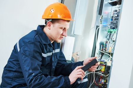 fuse box: electrician worker adjusting electonic equipment in fuse box Stock Photo