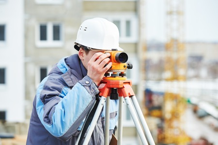 builder worker with theodolite transit equipment at construction site outdoors during surveyor work Stock Photo