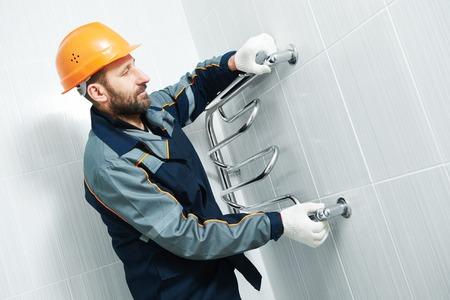 warmer: Plumbering service. plumber worker installing towel warmer