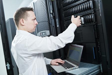 network engineer replacing hardware storage disk in server room