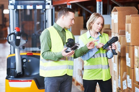 Male and female warehousing worker in storehouse with wireless barcode scanner. Warehouse Management System Фото со стока