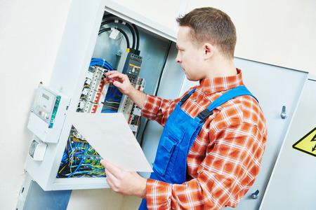 elektricien met elektrische schroevendraaier-test controle spanning van switching elektrische aandrijving apparatuur in zekeringkast
