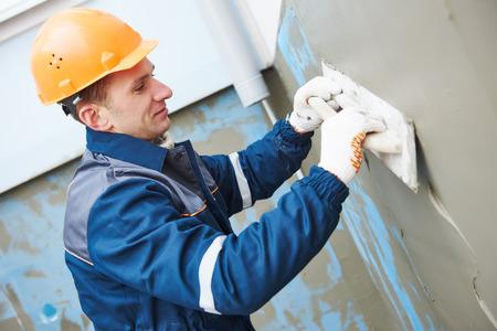 Fachada: Constructor en el trabajo de enlucido de fachada en el edificio industrial con el flotador espátula