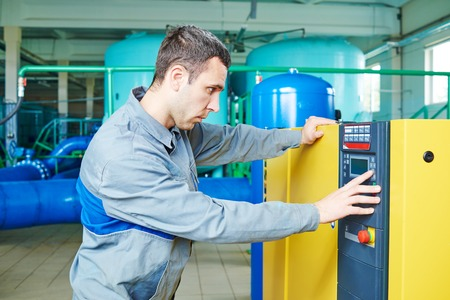 water purification plant: Worker serviceman operating industrial water purification filtration equipment in boiler room or treatment plant