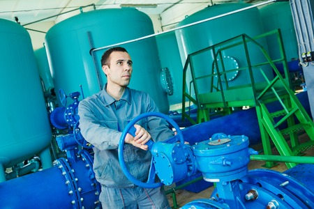 Worker serviceman operating industrial water purification filtration equipment in boiler room or treatment plant