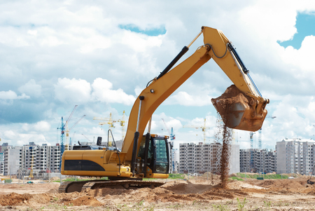 excavator machine loader doing earthmoving works at building construction site
