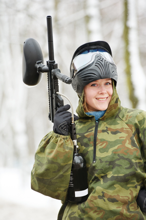 Female paintball player portrait with protective mask and comouflage clothing holding marker gun at winter outdoors