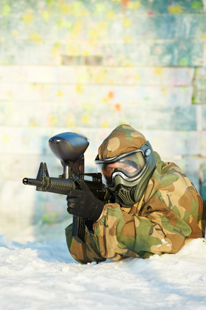 paintball extreme sport player wearing protective mask and comouflage clothing with marker gun at winter outdoors photo