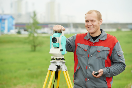 teodolito: industria de la topografía. sonriendo topógrafo positiva de trabajo con el equipo de tránsito teodolito en el sitio de construcción