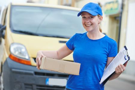 Souriant femelle courrier livraison femme courrier à l'extérieur en face de fourgonnette de livraison de colis Banque d'images - 64520276