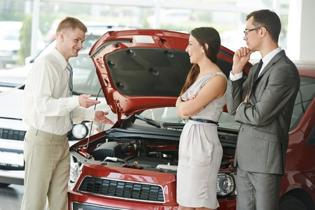 Family car shopping. Male salesperson demonstrating new automobile to young woman and man in showroom photo