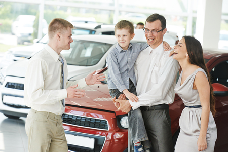 new automobile: Family car shopping. Male salesperson demonstrating new automobile to young woman and man in showroom Stock Photo