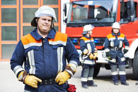 voiture de pompiers: pompier en uniforme devant la machine à moteur de feu et de l'équipe de pompier