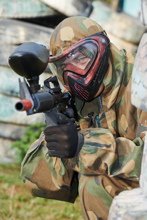 Adrenalin paintball player in protective uniform and mask aiming gun before shooting in summer Stock Photo