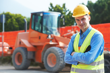construction worker in safety protective work wear at construction site in front of wheel loader machinery Stock Photo
