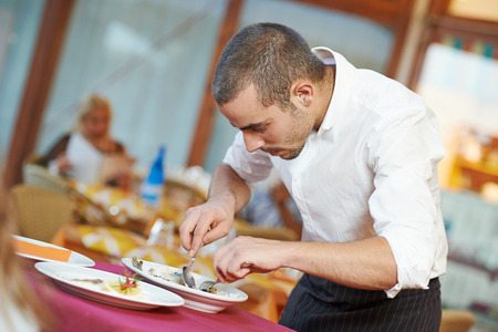 young male waiter prepairing fish food on tray serving at restaurant Stock Photo