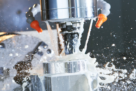 Milling metalworking process. Industrial precision CNC metal machining by vertical cutting mill with coolant Stockfoto