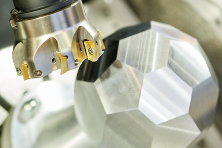 industrial metalworking machining cutting process. mill cutter with carbide inserts and multi shape metal detail at modern cnc machine