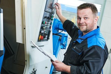 Industriële fabrieksarbeider of service monteur werkzaam cnc draaien schuim machine in de fabriek in metaal verspanende industrie