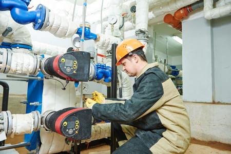 Plumber work. Construction worker installing water high pressure pump meter in boiler room