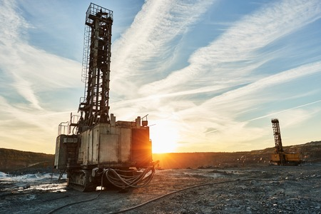 Rotary drill machines for the blasthole surface drilling mining industry in open pit at sunset